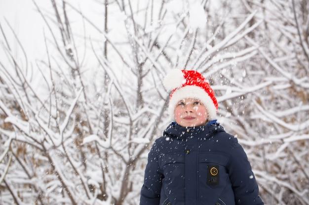 Garçon heureux en bonnet de noel dans le jardin en hiver
