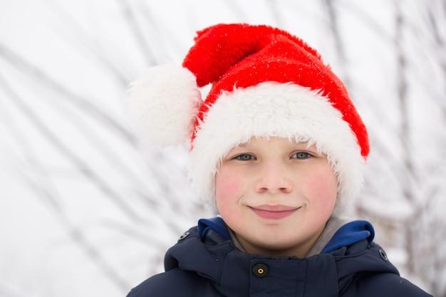 Garçon heureux en bonnet de noel dans la rue en hiver