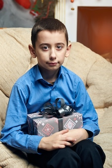 Un garçon heureux dans une chaise confortable près de l'arbre près de la cheminée a reçu un cadeau.