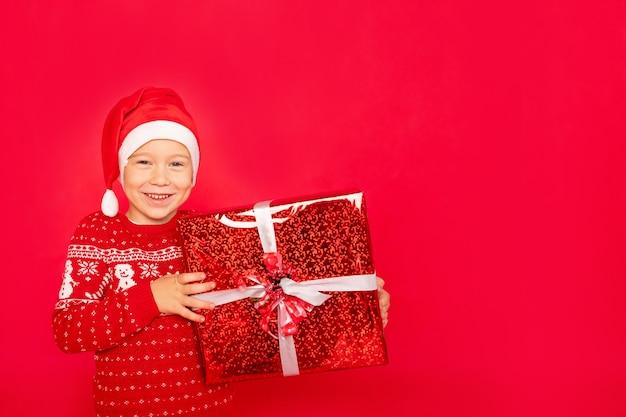 Un garçon heureux dans un pull et un bonnet de noel se dresse sur un fond rouge isolé avec un grand cadeau, un espace pour le texte