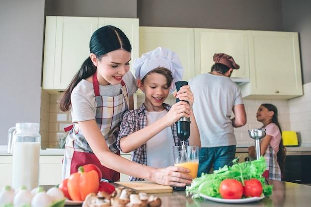 Un garçon heureux et excité mélange des œufs avec un mélangeur. sa maman tient une tasse où se trouvent les œufs. fille et papa se tiennent derrière eux. ils travaillent au poêle.