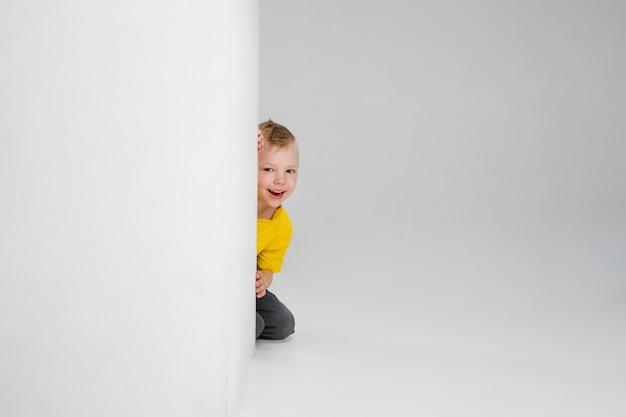 Garçon heureux isolé sur le mur. il a l'air heureux, joyeux. copyspace enfance, éducation, émotions, concept d'expression faciale. sauter haut, jouer en s'amusant