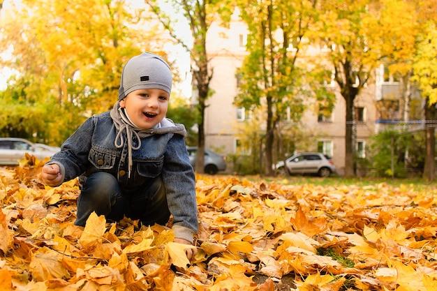 Le garçon heureux joue dans le feuillage d'automne