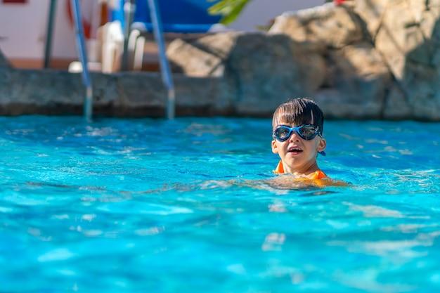 Un garçon heureux en lunettes de natation et volants de bras dans une piscine extérieure.