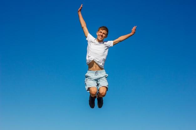 Garçon heureux, sautant dans le ciel bleu