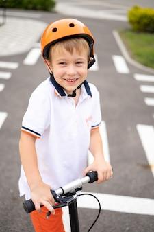 Un garçon heureux sur un scooter et portant un casque regarde la caméra et sourit