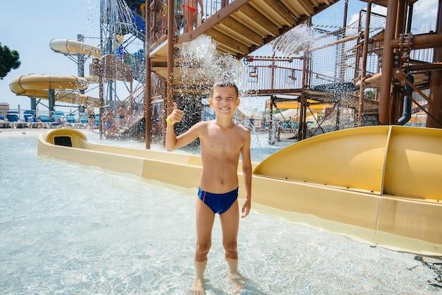 Un garçon heureux de sept ans sourit et montre une classe sur fond de toboggans dans un parc aquatique. bonnes vacances vacances. vacances d'été et tourisme.
