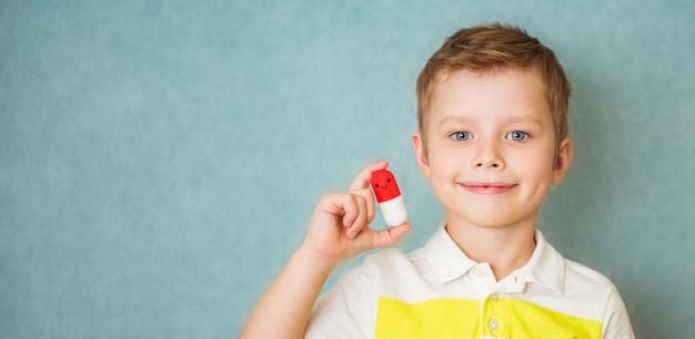 Garçon heureux souriant avec pilule à la main sur fond bleu