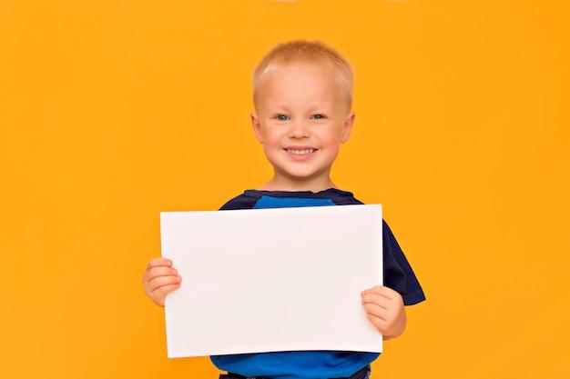 Garçon heureux avec un sourire tient une feuille blanche vierge. espace copie fond jaune