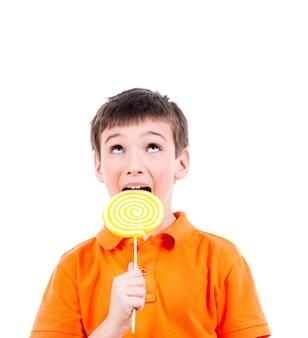 Garçon heureux en t-shirt orange, manger des bonbons colorés - isolé sur blanc