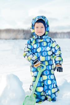Garçon en hiver avec une pelle en salopette se faufile dans le champ couvert de neige