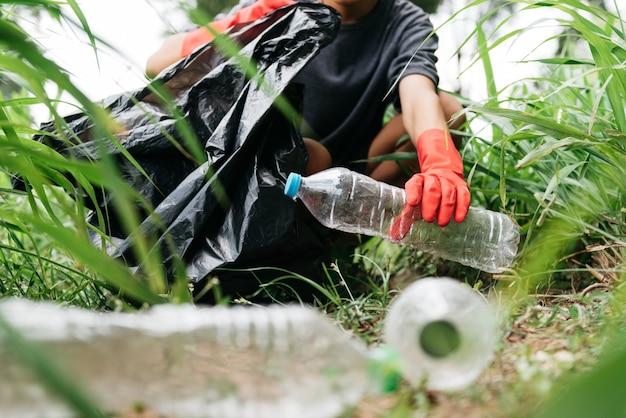 Garçon homme main ramasser une bouteille en plastique dans la forêt. concept de conservation de la nature et de l'environnement.