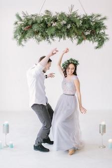Garçon d'honneur et demoiselle d'honneur vêtue d'une robe grise dansant dans une salle blanche avec des décorations de mariage