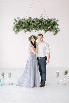 Garçon d'honneur et demoiselle d'honneur vêtue d'une robe grise debout dans une salle blanche avec des décorations de mariage