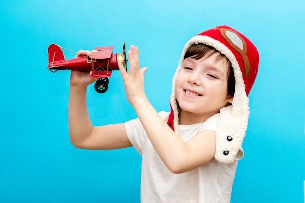 Un garçon impressionnant dans une casquette de pilote a levé les mains en tenant un avion jouet rétro, isolé sur un mur bleu. imagination d'un pilote, concept d'aviation