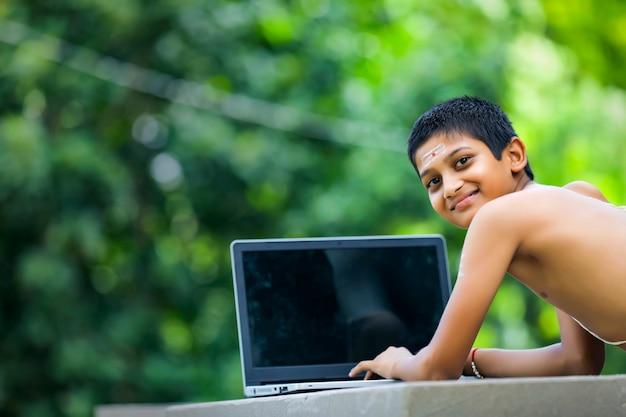 Garçon indien apprenant sur ordinateur portable