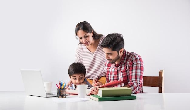 Garçon indien mignon avec père et mère étudiant ou faisant leurs devoirs à la maison à l'aide d'un ordinateur portable et de livres - concept de scolarisation en ligne