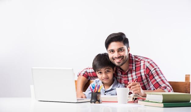 Garçon indien mignon avec père ou tuteur masculin faisant ses devoirs à la maison à l'aide d'un ordinateur portable et de livres - concept de scolarisation en ligne