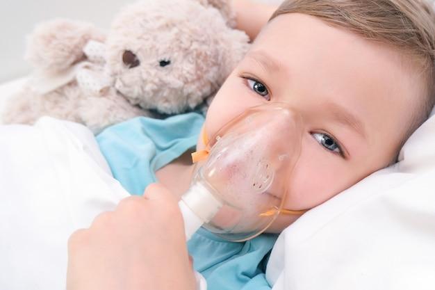 Le garçon a l'inhalation, procédure pour le traitement des poumons.