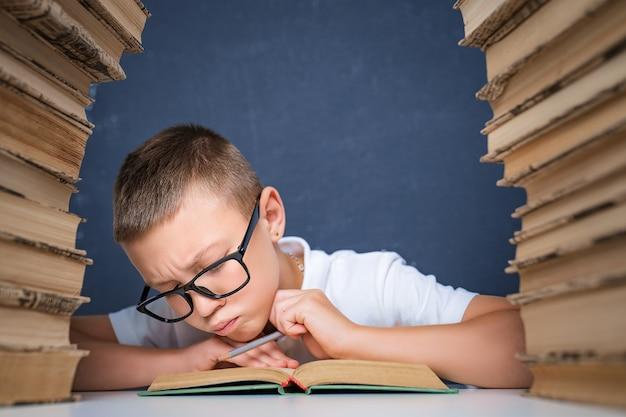 Garçon intelligent dans des verres assis entre deux piles de livres et lire attentivement le livre