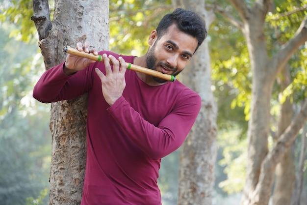 Un garçon intelligent a fière allure en jouant de la flûte