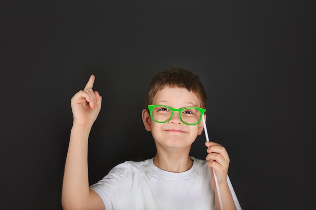 Un garçon intelligent avec des lunettes vertes est pensif près du tableau.