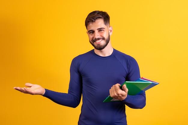 Garçon jeune étudiant sur fond jaune. garçon étudiant heureux