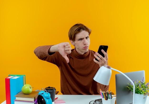Garçon jeune étudiant insatisfait assis au bureau avec des outils scolaires tenant le téléphone son pouce vers le bas sur jaune