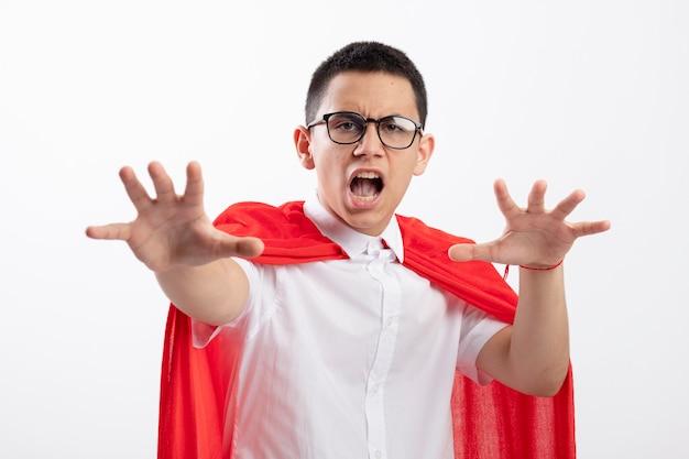 Garçon jeune super-héros insatisfait en cape rouge portant des lunettes regardant la caméra étirant les mains vers la caméra ne gesticulant pas isolé sur fond blanc