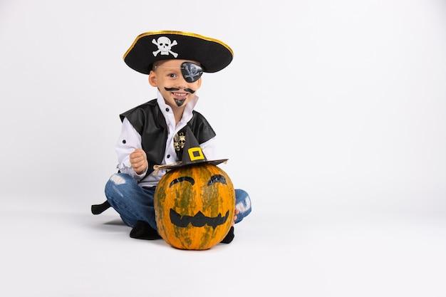 Garçon avec un joli sourire portant un chapeau de pirate. a proximité se trouve une citrouille dans un chapeau noir fait main. posant pour la caméra.
