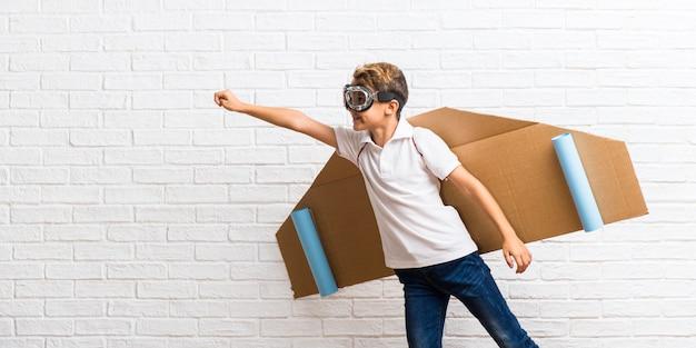 Garçon jouant avec des ailes d'avion en carton battant
