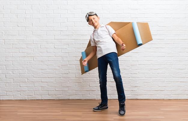 Garçon jouant avec des ailes d'avion en carton sur le dos, fier et satisfait de l'amour, concept vous-même