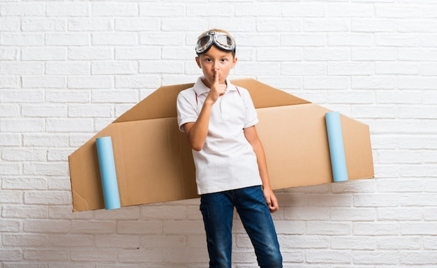 Garçon jouant avec des ailes d'avion en carton sur son dos, montrant un signe de fermeture de la bouche