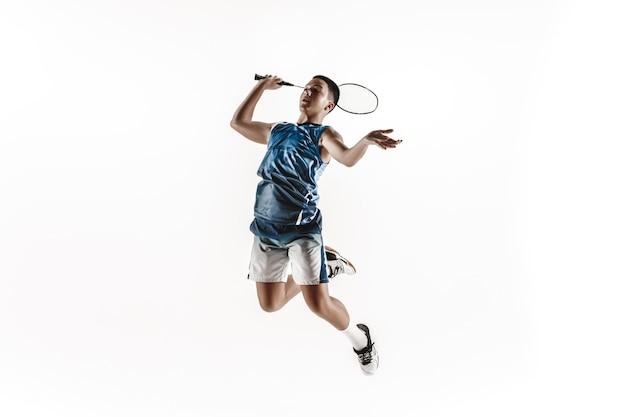 Garçon jouant au badminton isolé sur mur blanc.