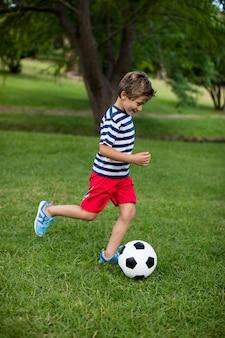 Garçon jouant au football dans le parc