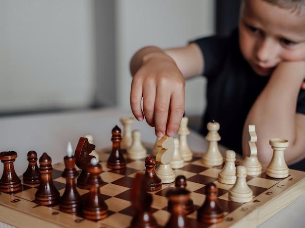 Le garçon jouant aux échecs dans la salle.
