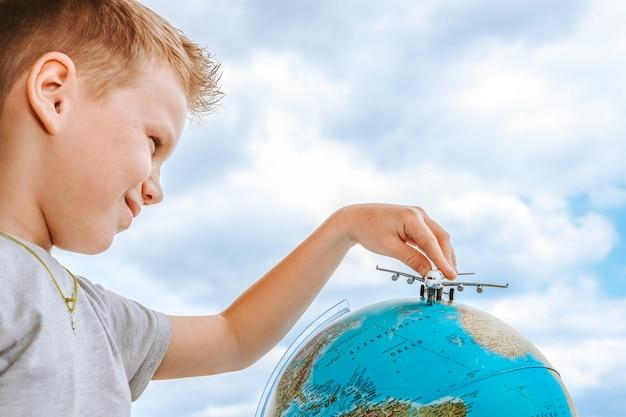 Le garçon jouant avec un avion jouet sur le globe.