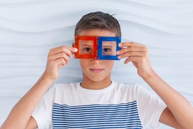Garçon jouant avec des blocs de jouets colorés le garçon a mis les détails du constructeur sur le visage comme des lunettes