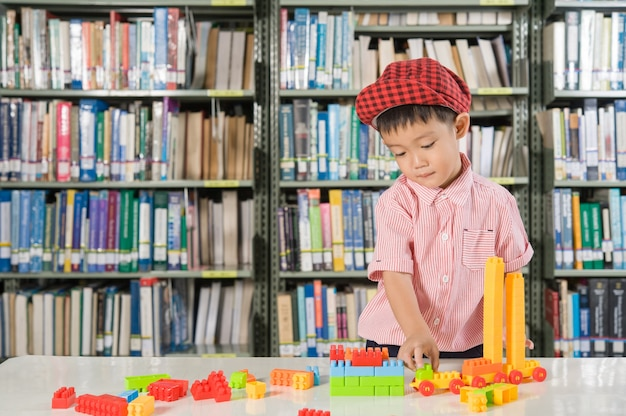 Garçon jouant avec des blocs de plastique dans l'école de la bibliothèque