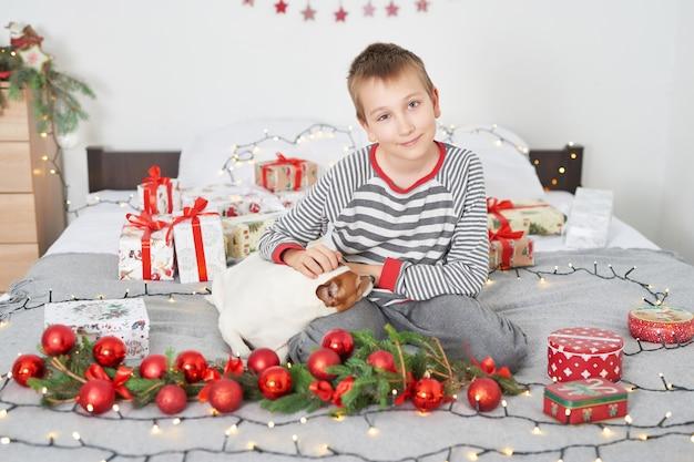 Garçon jouant avec chien jack russell sur un lit avec décoration du nouvel an