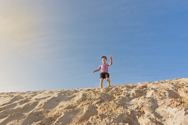 Garçon jouant dans les dunes