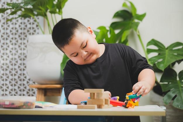 Le garçon jouant dans la maison avec monstera