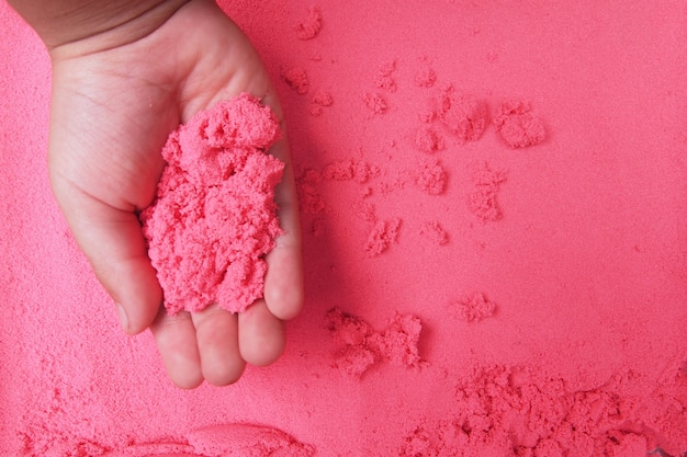 Un garçon jouant du sable rouge. texture de fond