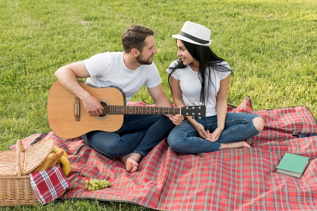 Garçon jouant de la guitare pour sa petite amie sur une couverture de pique-nique