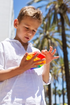 Garçon jouant avec un jouet anti-stress arc-en-ciel à l'extérieur