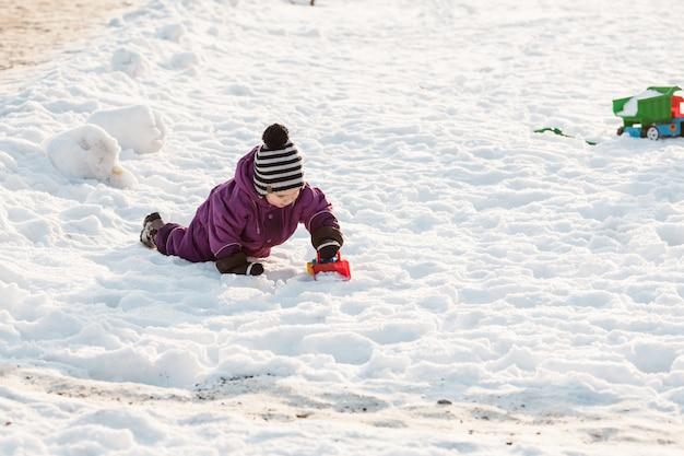 Garçon jouant avec un jouet chasse-neige. froide journée d'hiver