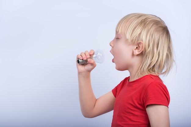Garçon jouant avec une lampe à incandescence. l'enfant chante dans une ampoule comme dans un microphone