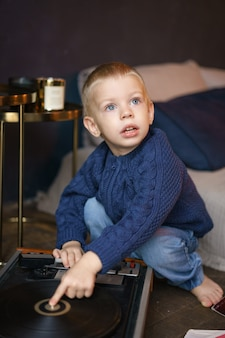 Garçon jouant avec lecteur de vinyle