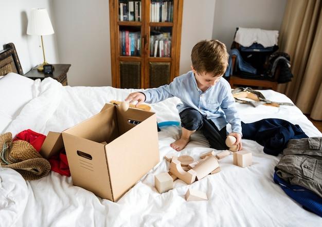 Garçon jouant sur le lit