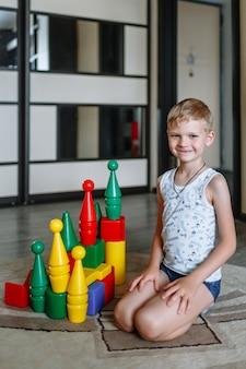 Un garçon jouant avec des personnages colorés à la maison